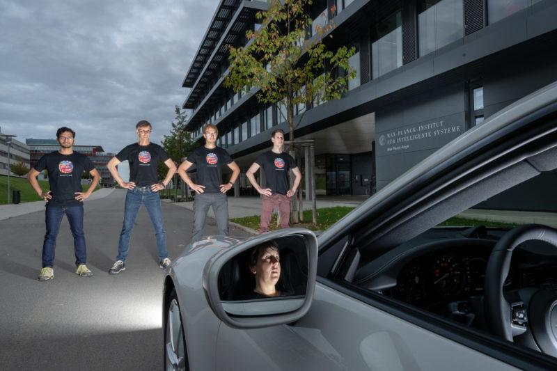 Pressefoto: Ein kleines Farbmuster kann autonom fahrende Autos stören. Ein Forscherteam steht vor einem Fahrzeug. Sie haben T-Shirts mit diesem von ihnen entwickelten Muster an. Im Außenspiegel sieht man die Fahrerin.