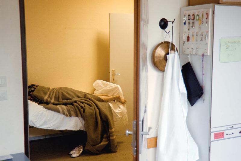 Reportagefotografie in der psychiatrischen Abteilung: Blick aus dem Dienstzimmer auf ein Patientenbett auf dem Flur, in dem zu dessen Überwachung jemand zugedeckt liegt. Man sieht nur die nackten Beine herausragen.