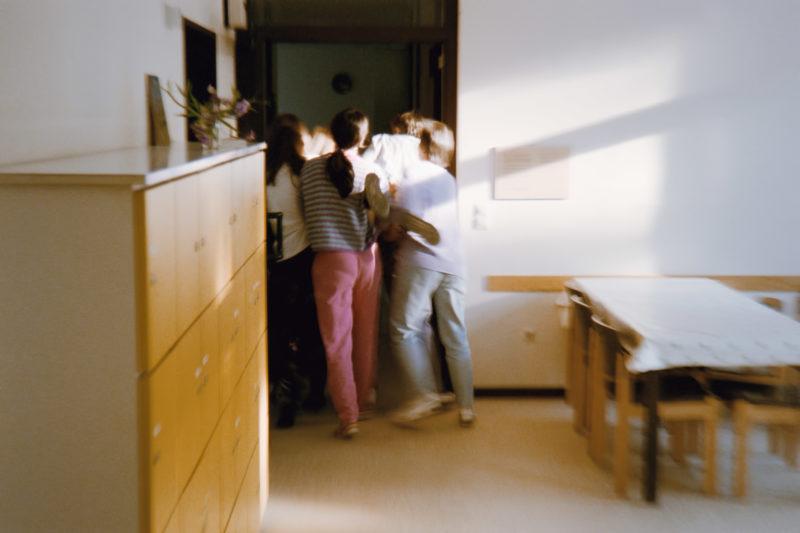 Reportagefotografie in der psychiatrischen Abteilung: Mehrere Pflegerinnen tragen eine Patientin der geschlossenen Station in ihr Zimmer, nachdem diese Personen angegriffen hat.