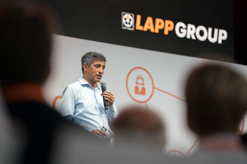 Event photography, editorial photography: The science journalist Ranga Yogeshwar gives a lecture at a Lapp Kabel event for guests, company employees and their families. In the background you can see the logo of the company.