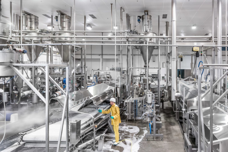 Industrial photography: Nightly high-pressure cleaning of a production plant for pastrys. One employee sprays all surfaces with a special disinfectant foam. The photo shows the complicated production line, built almost exclusively of stainless steel.