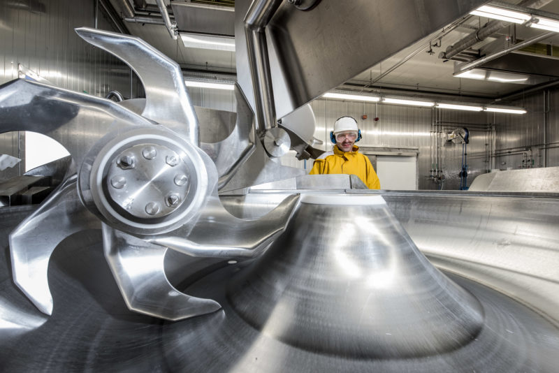 Industrial photography:  An employee of a cleaning company for food manufacturers in a yellow hygienic suit with protective goggles and helmet looks at a large meat cutter that is cleaned extremely thoroughly every night during the break.