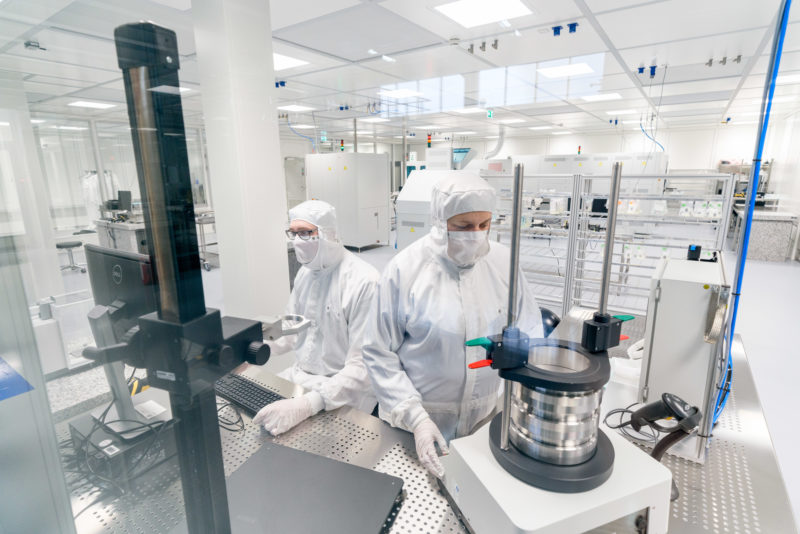 Industrial photography: View into a clean room for the production of electronic lighting elements at a manufacturer of illuminants. Two employees in white overalls with hood and face masks inspect components.