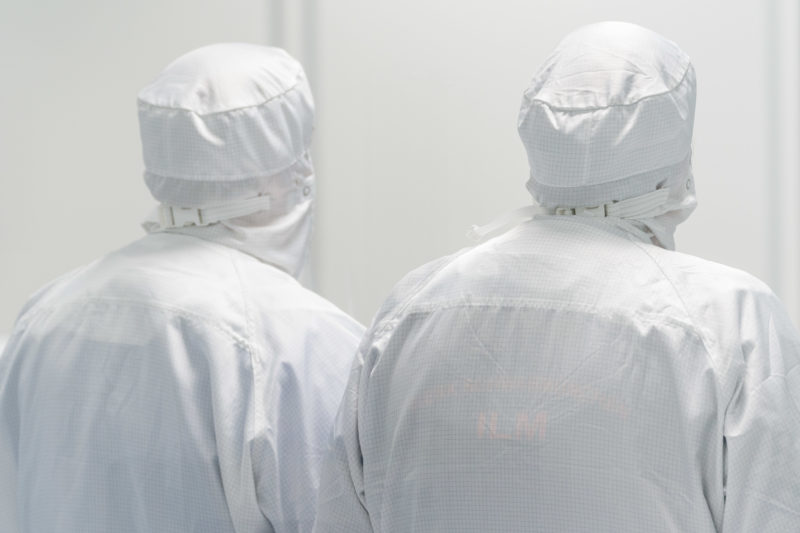 Industrial photography:  Two employees of a clean room photographed from behind. Through their white overalls and hoods the whole picture with the white background seems a bit unreal.