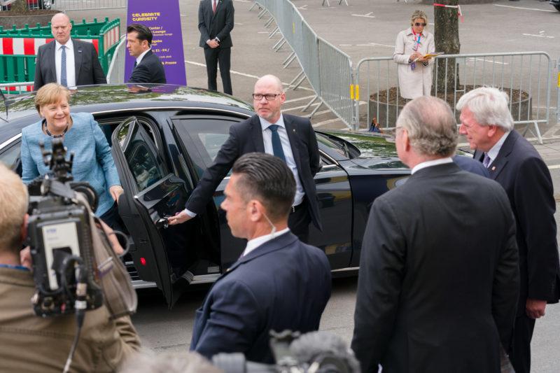 Reportagefotografie: Die Bundeskanzlerin Angela Merkel verlässt ihre Limousine um am Festakt eines Firmenjubiläums teilzunehmen. Sicherheitsleute, Gastgeber und der Ministerpräsident des Landes Hessen Volker Bouffier stehen zur Begrüßung bereit.