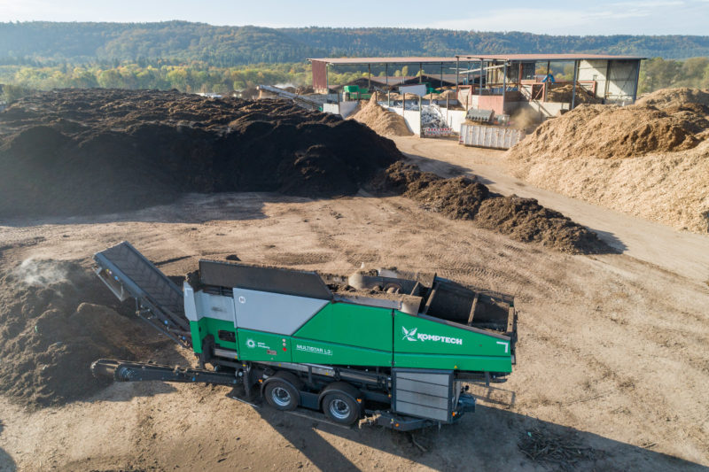 Reportage photography: drone photograph of a screening machine for compost waste working in a recycling company.
