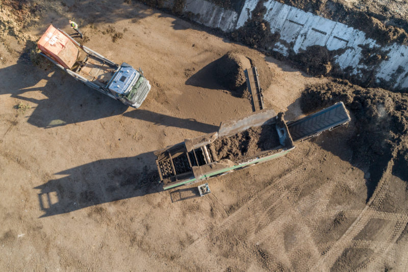 Reportage photography: A screening machine for compost waste with the drone photographed exactly vertically from above.