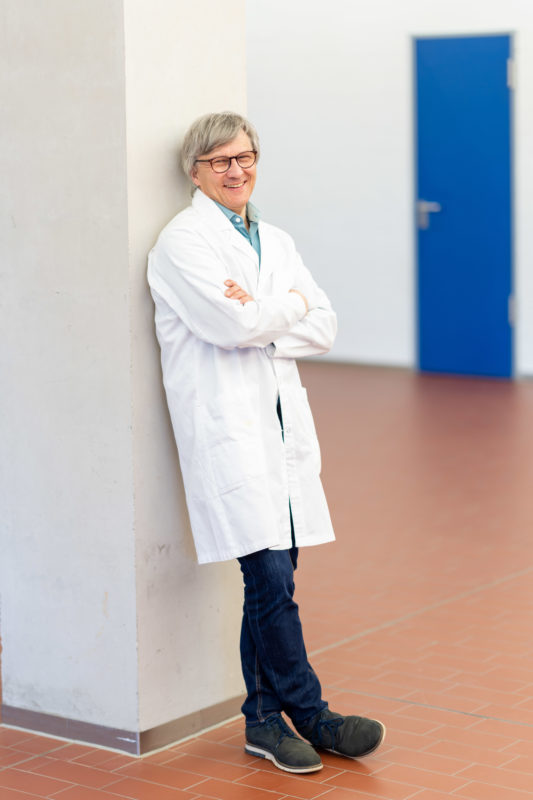 Reportage photography: Scientists create artificial ivory: Single portrait of the male scientist in a white lab coat.