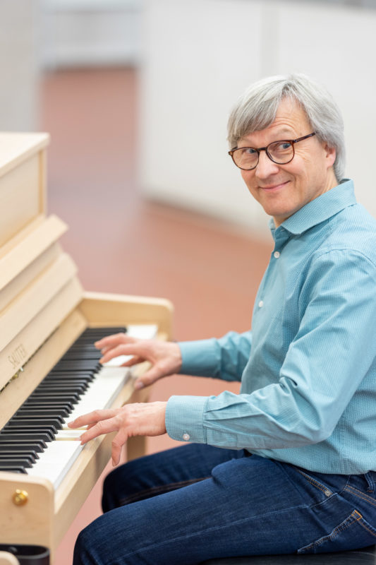 Reportage photography: Scientists create artificial ivory: One of the scientists is playing with pleasure on the piano, whose keys were made of the new material.