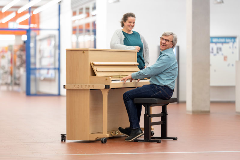 Reportage photography: Scientists create artificial ivory: piano with keys made of artificial ivory. One of the scientists plays with it in the corridor at his institute.