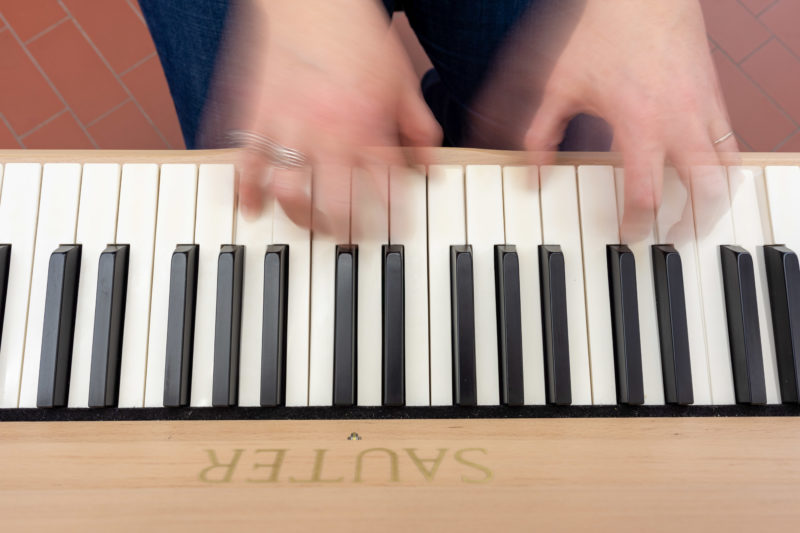 Reportage photography: Scientists create artificial ivory: Photo of a piano keyboard from above with artificial ivory and the moving hands of a player.