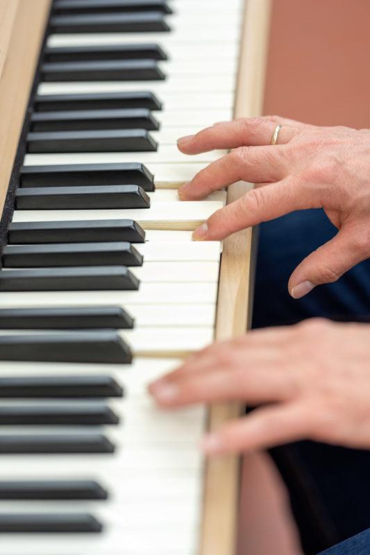 Reportagefotografie: Wissenschaftler erzeugen künstliches Elfenbein: Hochformat der Klaviatur mit weissen Tasten aus dem neuen Material. Man sieht die Hand des Spielers.