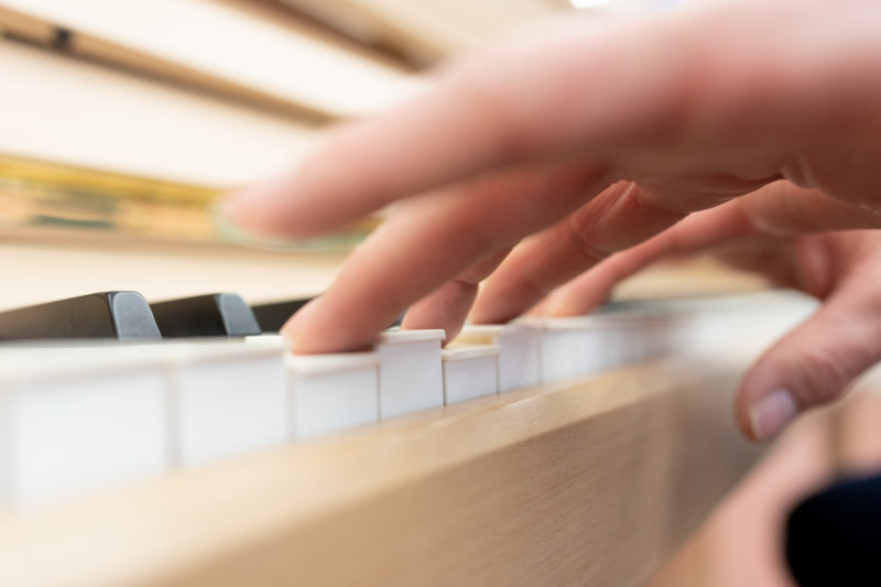 Reportage photography: Scientists create artificial ivory: Landscape format of the keyboard with white keys made of the new material. You can see the hand of the player.