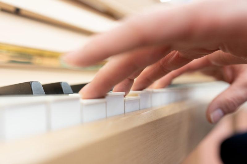 Reportagefotografie: Wissenschaftler erzeugen künstliches Elfenbein: Querformat der Klaviatur mit weissen Tasten aus dem neuen Material. Man sieht die Hand des Spielers.