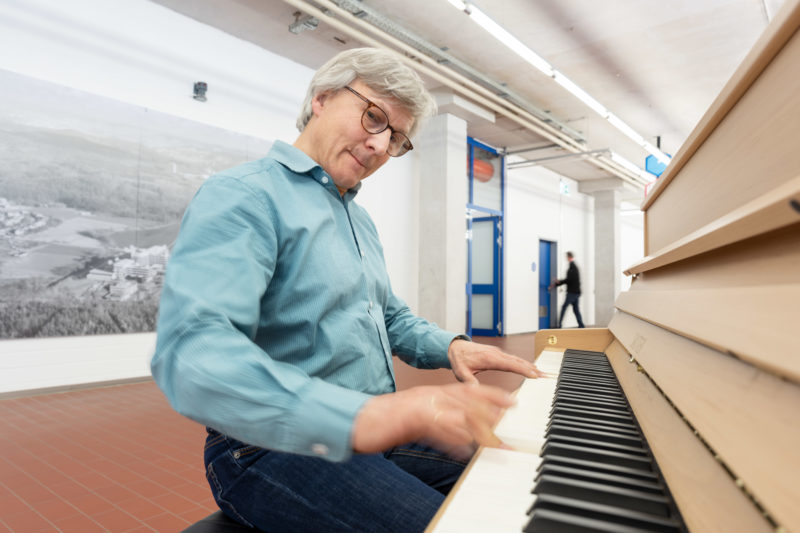 Reportage photography: scientists create artificial ivory: portrait of one of the scientists. He sits at the piano with keys made of the new material.