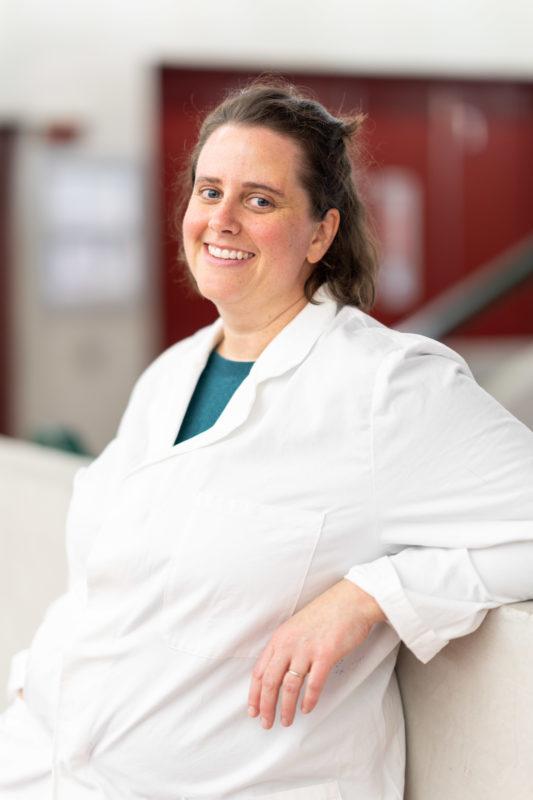 Reportagefotografie: Wissenschaftler erzeugen künstliches Elfenbein: Entspanntes Einzelportrait der weiblichen Wissenschaftlerin in ihrem weißen Laborkittel.