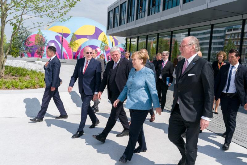 Reportagefotografie: Bundeskanzlerin Angela Merkel auf der Feier zum 350jährigen Jubiläum der Firma Merck in Darmstadt. Die VIP-Gäste gehen zusammen mit ihr zur Firmenbesichtigung. Im Hintergrund das extravagante Festzelt.