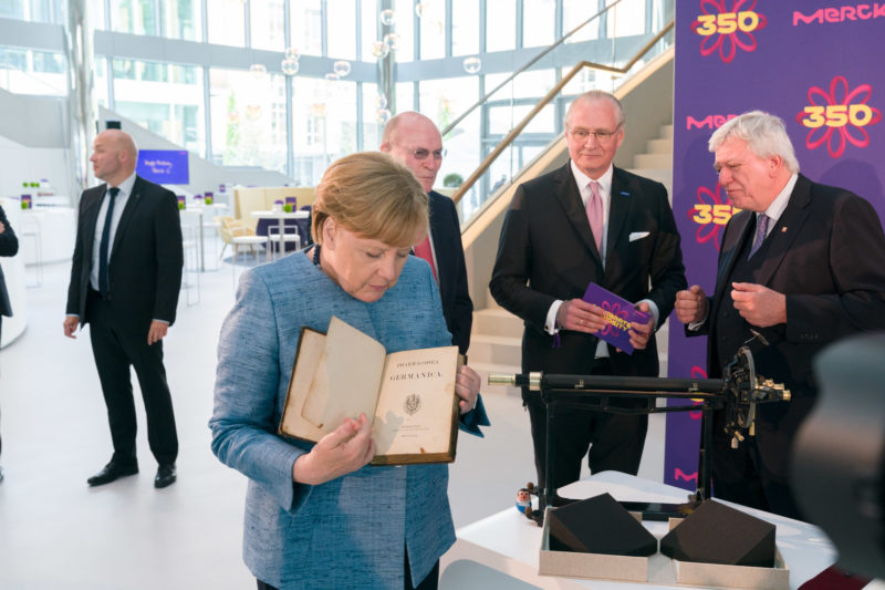editorial photography:  German Chancellor Angela Merkel at the celebration of the 350th anniversary of Merck in Darmstadt. She is looking at a book from the company