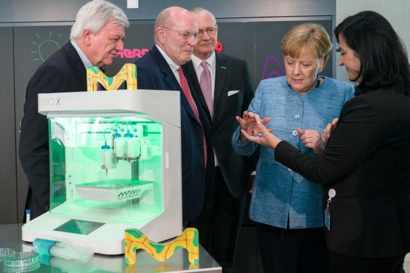 Reportagefotografie: Bundeskanzlerin Angela Merkel auf der Feier zum 350jährigen Jubiläum der Firma Merck in Darmstadt. Eine Mitarbeiterin zeigt ihr ein chemisches Produkt.