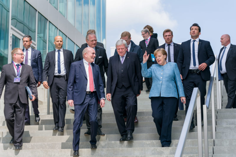 editorial photography: German Chancellor Angela Merkel at the celebration of the 350th anniversary of Merck in Darmstadt. At the end of the event, she and her hosts walk down the stairs to the street where her vehicle is waiting.