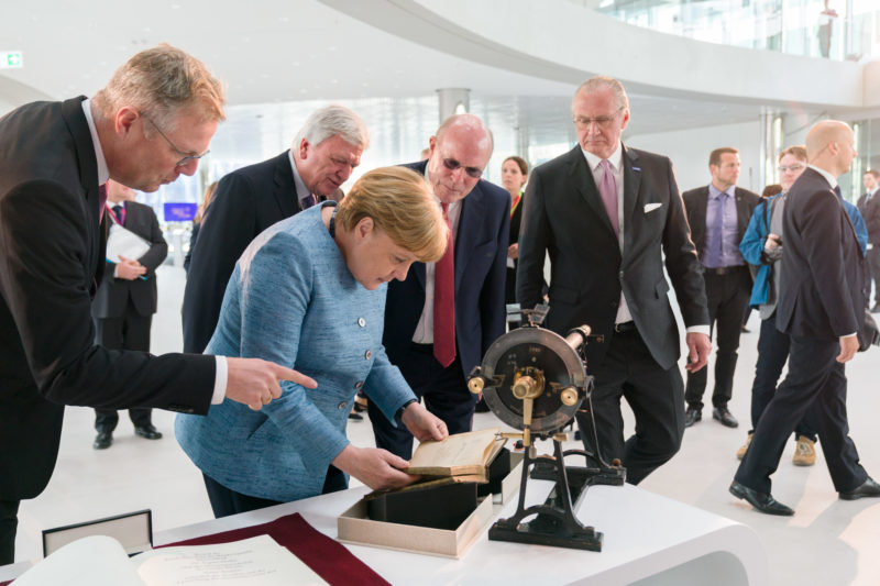 editorial photography: German Chancellor Angela Merkel at the celebration of the 350th anniversary of Merck in Darmstadt. She is looking at a book and other exhibits about the company
