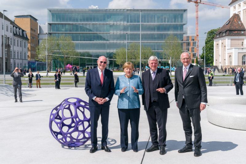 Reportagefotografie: Bundeskanzlerin Angela Merkel auf der Feier zum 350jährigen Jubiläum der Firma Merck in Darmstadt. Die Gastgeber stoppen mit ihr für ein Gruppenfoto vor der Firmenzentrale.