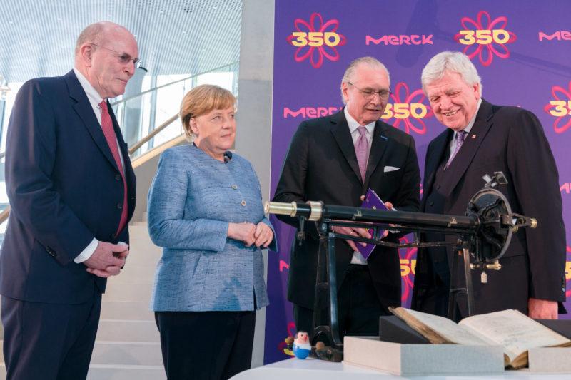 Reportagefotografie: Bundeskanzlerin Angela Merkel auf der Feier zum 350jährigen Jubiläum der Firma Merck in Darmstadt. Zusammen mit Volker Bouffier unterhält sie sich mit den Firmenchefs. Im Vordergrund sieht man Gegenstände aus der Gründergeschichte.