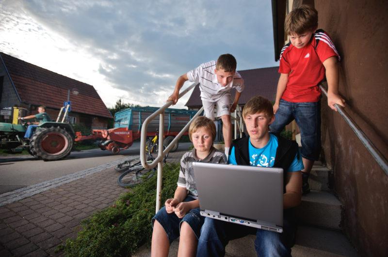 Reportage-Fotografie: Jugendliche in einem Dorf surfen mit einem Notebook mobil im Internet.