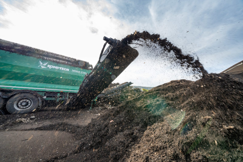 Reportage photography: A screening machine for compost waste spits screened earth onto a heap. The camera is right in the middle of it. Dust and dirt flies everywhere.
