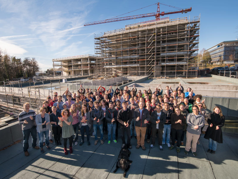 Group photo: The future users of a new building celebrate the shell construction of the building. They applaud while in the background the building with construction crane and scaffolding can be seen. In the foreground is the dog, which is allowed to move into the new office during the working hours of its owner.