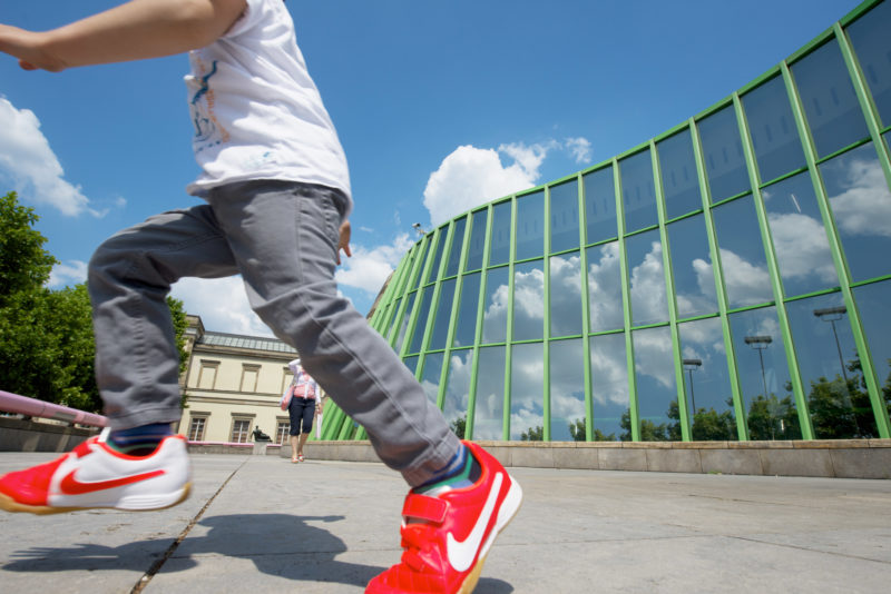 A boy in red sneakers jumps over the forecourt of the Staatsgalerie Stuttgart. Clouds are reflected in the curved glass front of the foyer against a blue sky. In the background a passer-by and, very small, the sculpture Draped Reclining Woman by Henry Moore is visible.
