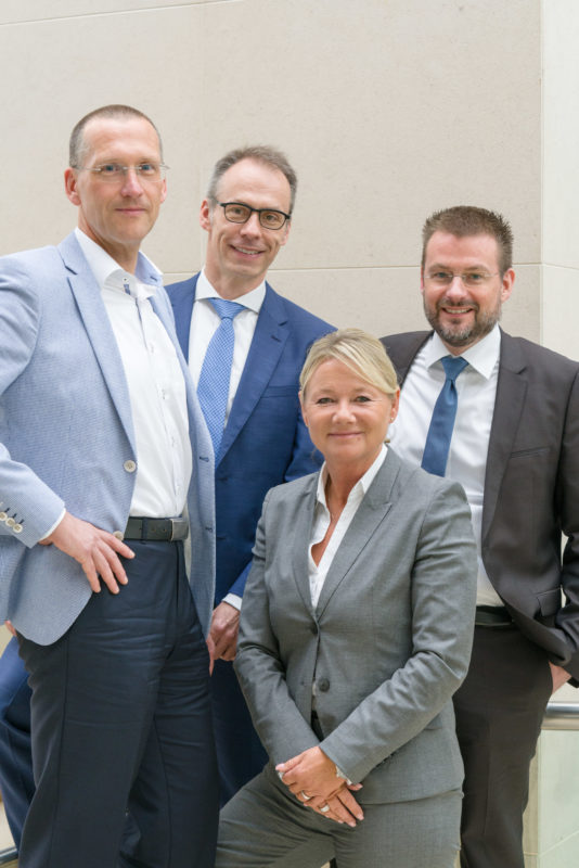 Group photo:  Four conversational partners of a roundtable discussion, photographed in the foyer of a hotel before the start of the event.