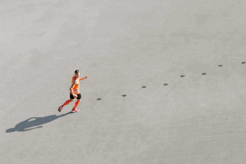 Photomontage with Photoshop: A reverse running athlete runs over the asphalt and leaves wet footprints.