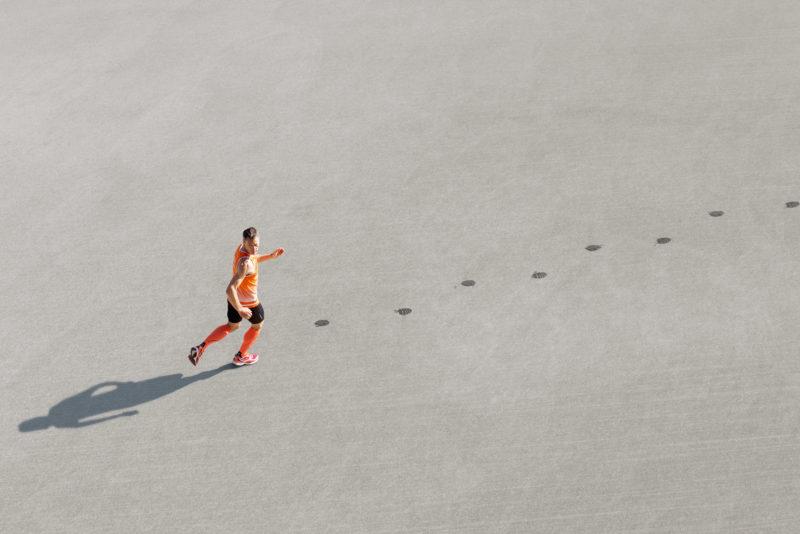 Fotomontage mit Photoshop: Ein Rückwärtslauf-Sportler läuft über den Asphalt und hinterlässt dabei feuchte Fusspuren.