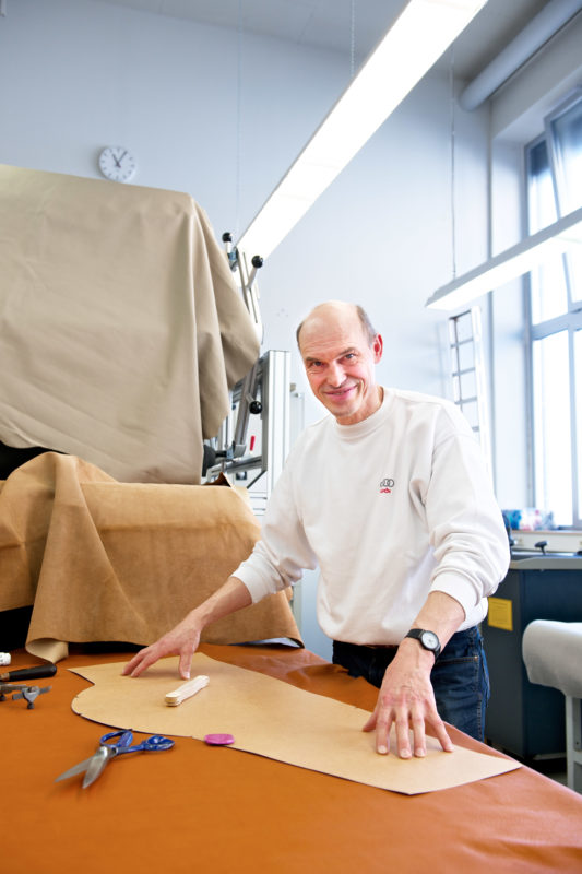 Employees photography: A leatherworker at a big car manufacturer. He works on special requests of customers and for test vehicles in development. In front of him a piece of light-coloured leather sewn into the side wall of a seat.