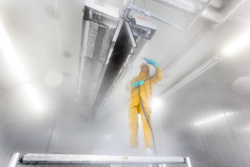 Industrial photography: High pressure cleaning of a large plant of a food manufacturer almost completely made of stainless steel. With special foam every surface is intensively cleaned and disinfected at the same time.