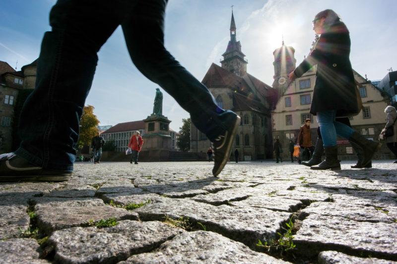 Stadtportrait Stuttgart: Auf dem Schillerplatz in Stuttgart laufen Passanten mit großen Schritten über den sonnendurchfluteten Platz. Im Hintergrund die Silhouette der Stiftskirche.