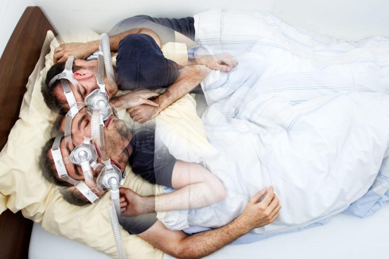 Fotomontage mit Photoshop: Ein Mann wälzt sich nachts im Bett eines Schlaflabors. Er hat eine Atemmaske auf dem Gesicht.