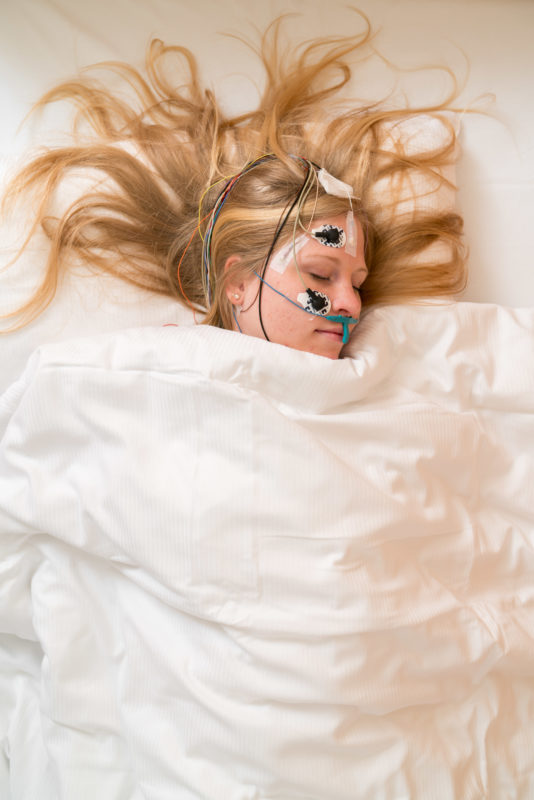 Science photography: A test subject lies in bed in the sleep laboratory at the University Hospital Freiburg, Department of Psychiatry and Psychotherapy. Her head is equipped with electrodes to measure brain activity and breath.
