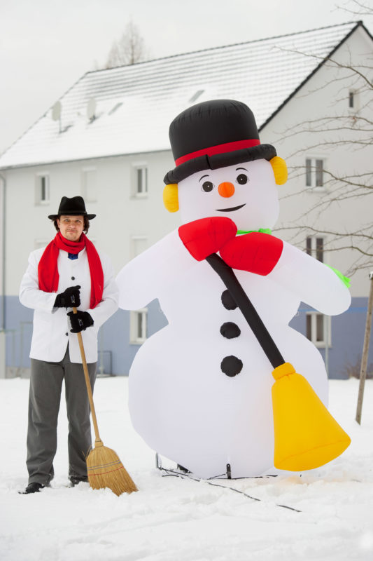 Employees photography: As a hobby this man collects snowmen from all over the world. Here he stands in the same pose and clothing next to the largest figure of his collection in the snow.