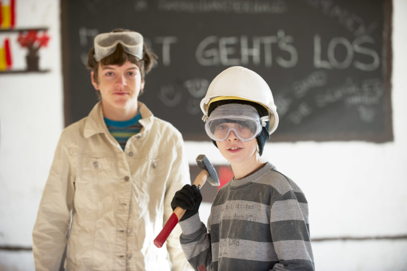 Editorial photography: Two students in an educational project helping to renovate an old house. The boy in the foreground wears a construction helmet and a heavy hammer. They both wear safety goggles.