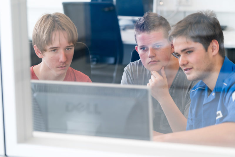 Editorial photography: A trainee explains a computer program to two pupils during an internship. This gives them an impression of the in-company training.