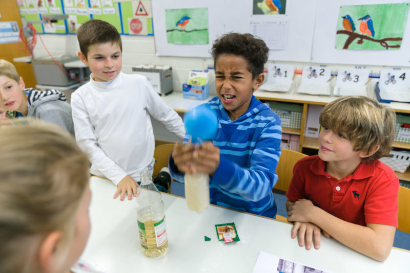 Editorial photography, subject learning and education: In an experiment with a bottle of water, some vinegar, baking powder and a balloon, schoolchildren playfully learn about chemistry.