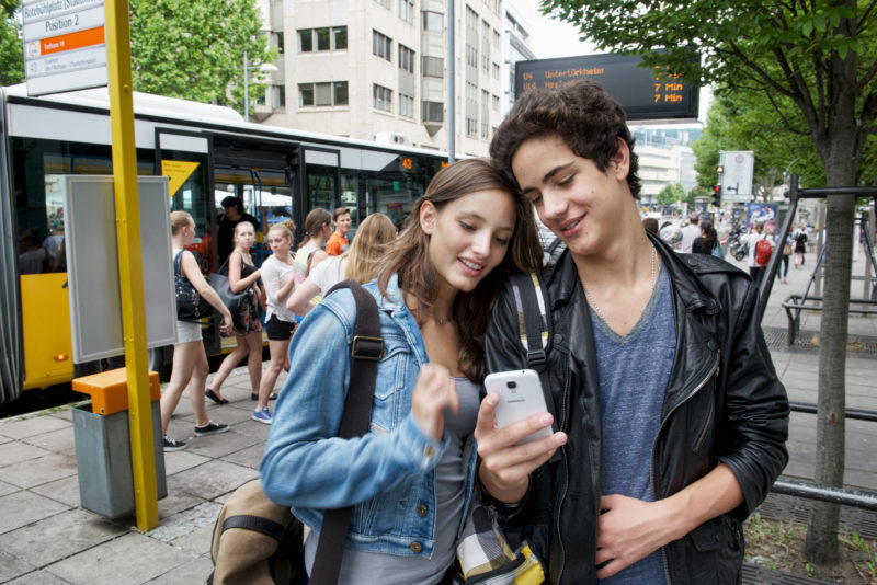 Lifestyle-Fotografie: Eine Schülerin und ein Schüler schauen an einer Bushaltestelle in ein Smartphone.