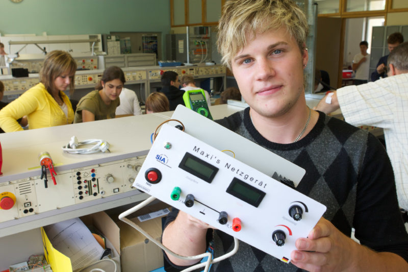 Editorial photography: At a secondary school, students work in the electronics laboratory. One of them holds his selfmade power supply into the camera, which is labeled with his name.