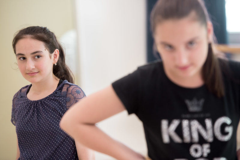 Editorial photography: Two girls of a school theatre project during a rehearsal. Their faces show the commitment with which they are involved. The girl on the right front is blurred to focus on the girl on the left.