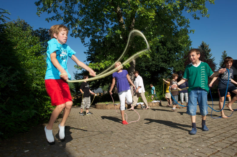 Editorial photography: Primary school children volunteer for sports during the break. Several of them do rope-hopping together in the schoolyard. The weather is fine and the sun is shining. Everybody