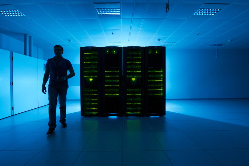 Industrial Photography: Server In a data center. An employee walks past the black cabinet in which a lot of green lights shine.