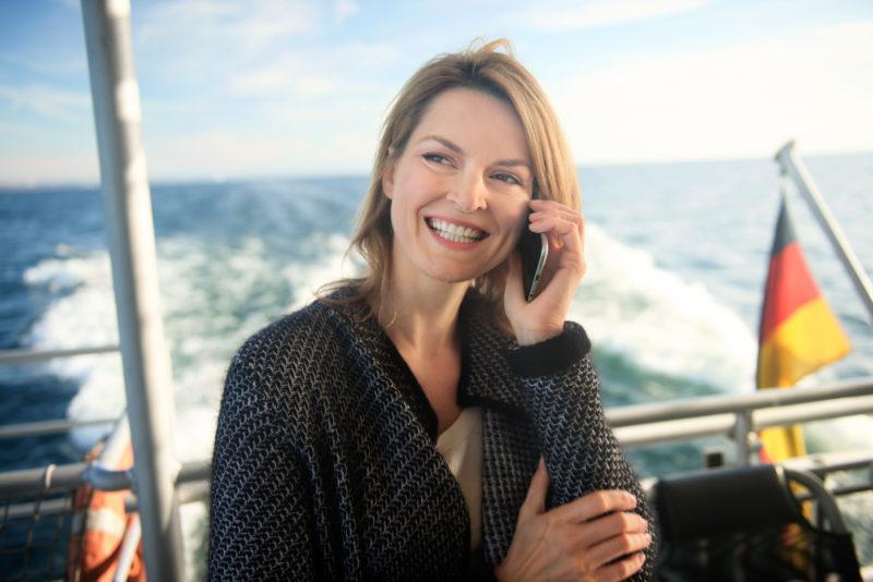 Industriefotografie: Eine Frau telefoniert mit ihrem Smartphone an Bord eines Schiffes. Im Hintergrund die deutsche Fahne am heck des Bootes.