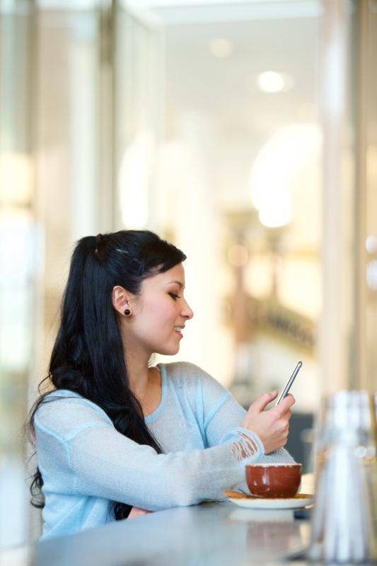 Lifestyle-Fotografie: Eine junge Frau sitzt in einem Cafe und freut sich über eine Nachricht, die auf Ihrem Smartphone eingeht, das sie in der Hand hält.